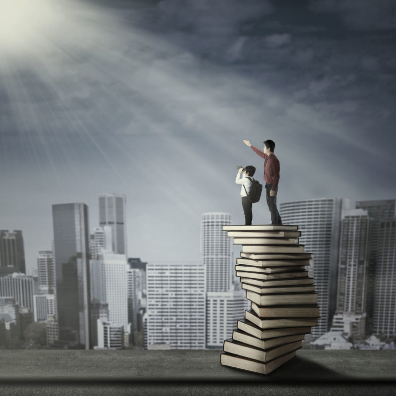 27898963 - businessman with little child standing on a stack of books