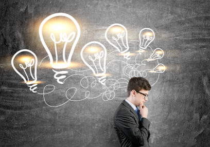 58472065 - idea concept with thoughtful businessman standing against chalkboard with illuminated lightbulb sketches